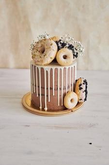 Vertikale nahaufnahmeaufnahme des köstlichen donut-schoko-geburtstagskuchens mit donuts oben und weißem tropfen