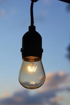 Vertikale nahaufnahmeaufnahme einer brennenden glühbirne gegen den bewölkten himmel