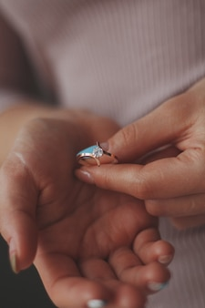 Vertikale nahaufnahmeaufnahme einer frau, die einen schönen golddiamantring hält