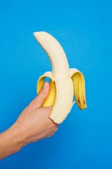 Vertikale nahaufnahmeaufnahme einer person, die eine geschälte banane gegen eine blaue wand hält