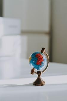 Vertikale nahaufnahmeaufnahme eines dekorativen kleinen globus auf einem weißen schreibtisch und verwischt