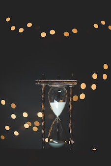 Vertikale nahaufnahmeaufnahme eines sandglas-timers mit grellen lichtern im hintergrund
