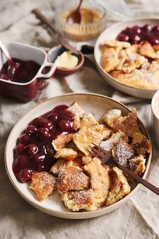 Vertikale nahaufnahmeaufnahme von köstlichen flauschigen pfannkuchen mit kirsche und puderzucker