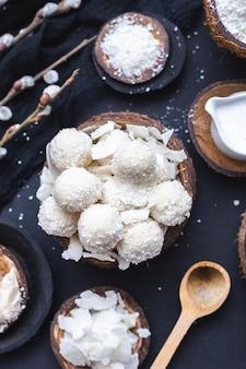 Vertikale nahaufnahmeaufnahme von rohem raffaello in einer holzschale mit kokosnussstücken und einem holzlöffel