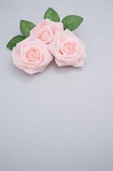 Vertikale nahaufnahmeaufnahme von rosa rosen lokalisiert auf einem blauen hintergrund mit kopienraum