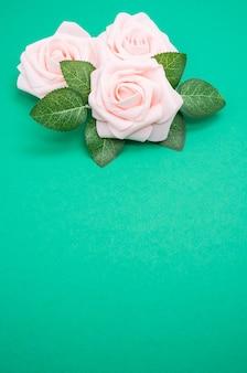 Vertikale nahaufnahmeaufnahme von rosa rosen lokalisiert auf einem grünen hintergrund mit kopienraum