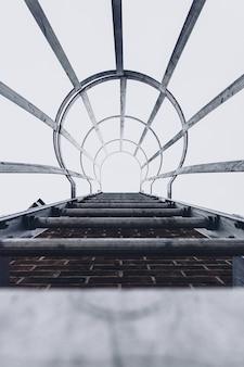 Vertikale niedrige winkelaufnahme einer feuer-metalltreppe auf einer ziegelmauer mit einem stahlsicherheitskäfig.