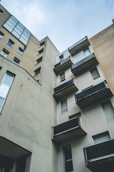 Vertikale niedrige winkelaufnahme eines braunen abstrakten architekturgebäudes mit balkonen und fenstern