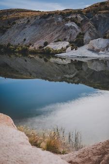 Vertikale schöne szene eines blauen sees, umgeben von bergen