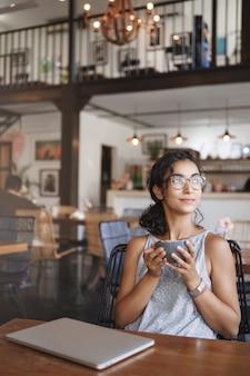 Vertikale schuss sanfte zarte entspannte städtische frau, die brille trägt, genießt moment, der allein im café sitzt