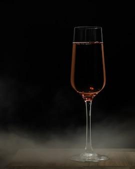 Vertikale selektive fokusaufnahme eines glases champagner auf einer holzoberfläche und einer schwarzen entfernung