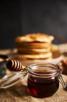 Vertikale selektive fokusaufnahme eines glases honig mit apfelpfannkuchen auf dem hintergrund