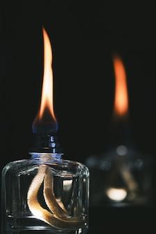 Vertikale selektive fokusaufnahme von zwei alkoholfeuerzeugen lokalisiert auf einem schwarzen hintergrund