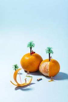 Vertikale selektive fokusnahaufnahme von spielzeugleuten, kokospalmen und frischer mandarine