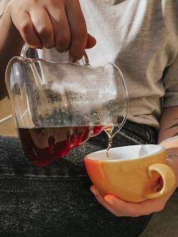 Vertikale selektive nahaufnahmeaufnahme einer person, die tee in eine gelbe keramikschale gießt