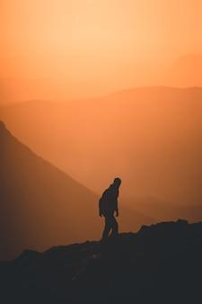 Vertikale silhouette einer person, die bei sonnenuntergang den hügel hinaufklettert