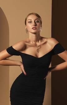 Vertikale studioaufnahme des attraktiven mädchens im schwarzen kleid und im tragen der goldenen halskette und der ohrringe