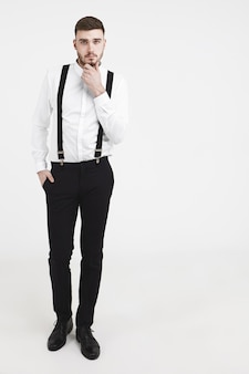 Vertikale studioaufnahme in voller länge von elegantem, hübschem, jungem, bärtigem, männlichem model, das schwarze hosen, schuhe und ein weißes hemd mit hosenträgern trägt, die seine stoppeln berühren und für den herrenmode-katalog posieren
