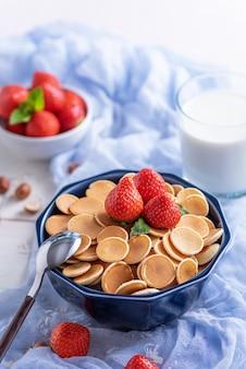 Vertikale trendige müsli-pfannkuchen in blauer schüssel mit erdbeeren und haselnüssen, löffel auf blauer gaze auf weißem holz