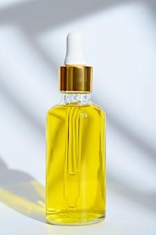 Vertikale tropferglasflasche mit gelbem kosmetischem öl auf weißem hintergrund
