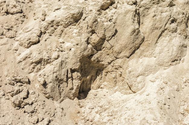 Vertikale wand einer sandgrube als natürlicher hintergrund gelber sand