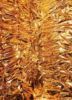 Vertikale zerknitterter goldfolienpapier-beschaffenheitshintergrund.