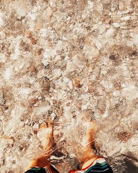 Vertikale zusammensetzung der touristischen füße unter wasser in transparentem ozeanstrand - sommerurlaubsurlaubsmann, der strand genießt