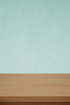 Vertikaler brauner holztisch und grüner zementwandhintergrund in der küche