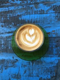 Vertikaler cappuccino mit hohem winkel auf einer blauen holzoberfläche