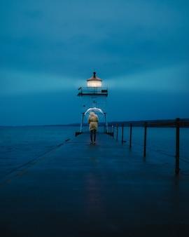 Vertikaler entfernter schuss einer person, die einen regenschirm hält, der auf einem steg nahe einem leuchtturm geht