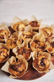 Vertikaler hochwinkelschuss des köstlichen schokoladenmuffins auf einem holzteller auf einem weißen tisch