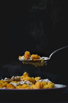 Vertikaler hochwinkelschuss eines köstlichen heißen gerichts mit reis, huhn und gelber soße