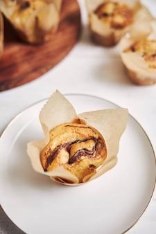 Vertikaler hochwinkelschuss eines köstlichen schokoladenmuffins nahe einer hölzernen platte auf einer weißen platte
