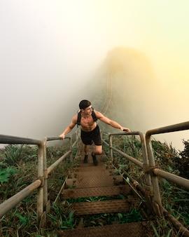 Vertikaler hochwinkelschuss eines mannes, der die treppe auf einem hügel hinaufsteigt - herausforderungskonzept überwindet