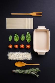 Vertikaler hochwinkelschuss von lasagne-zutaten, kräutern, käse und gemüse auf einer schwarzen oberfläche
