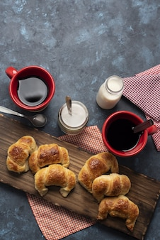 Vertikaler hochwinkelschuss von mini-croissants auf einem holzschreibtisch und zwei roten tassen kaffee