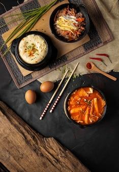 Vertikaler hochwinkelschuss von schalen od hummus, gemüse und suppe auf einem schwarzen tisch
