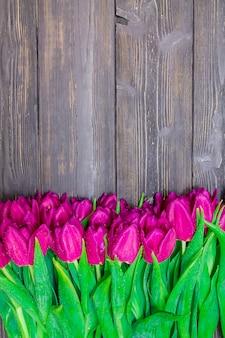 Vertikaler kopienraum des frauentages mit hellen rosa tulpen auf einem schwarzen hölzernen hintergrund