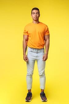 Vertikaler männlicher hippie-kerl des schusses in voller länge, hispanische ethnie, beiläufig gelber hintergrund stehend, tragen stilvolles orange t-shirt, weiße hosen, schauen die kamera ohne ausdruck und lächeln etwas