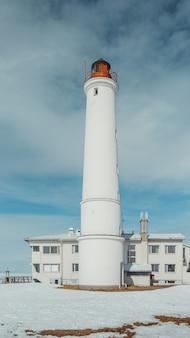 Vertikaler niedriger winkel eines weißen leuchtturms unter dem bewölkten himmel
