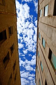 Vertikaler niedriger winkelschuss zwischen zwei gebäuden mit bewölktem himmel