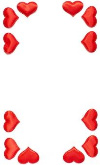 Vertikaler rahmen gemacht von den roten herzen lokalisiert auf weißem hintergrund, valentinstagkonzept. flach liegen