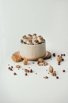Vertikaler rahmen hausgemachter geburtstagskuchen schöner kuchen mit walnüssen schokoladenbiskuitkuchen mit frischkäse und nüssen