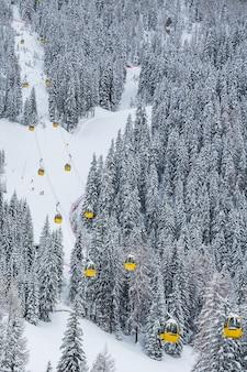 Vertikaler schuss der gelben seilbahnen im berg während des winters