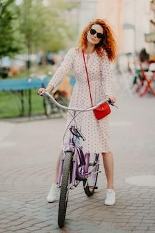 Vertikaler schuss der gelockten rothaarigen frau fährt fahrrad in der stadt während weeked, hat freizeit