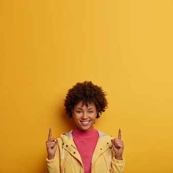 Vertikaler schuss der glücklich lächelnden dunkelhäutigen frau zeigt oben mit beiden zeigefingern, gibt empfehlung oder rat, schlägt vor, dieser richtung zu folgen, gekleidet in jacke, isoliert auf gelber wand