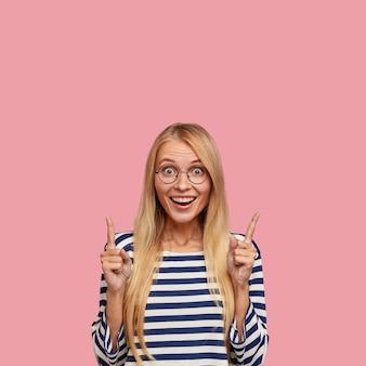 Vertikaler schuss der glücklichen blonden frau, die gegen die rosa wand aufwirft