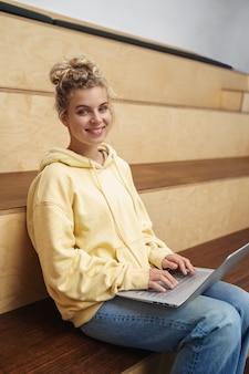 Vertikaler schuss der lächelnden studentin, die vortrag auf laptop aufschreibt.