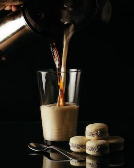 Vertikaler schuss der person, die tee und milch in ein glas auf dem tisch mit keksen gießt