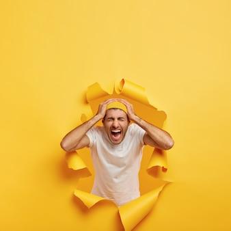 Vertikaler schuss des emotionalen kerls berührt kopf mit beiden händen, trägt lässiges weißes t-shirt, stilvollen gelben hut